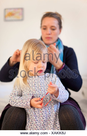 Mother doing daughters hair - Stock Photo