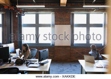 Business people working at desks in office - Stock Photo