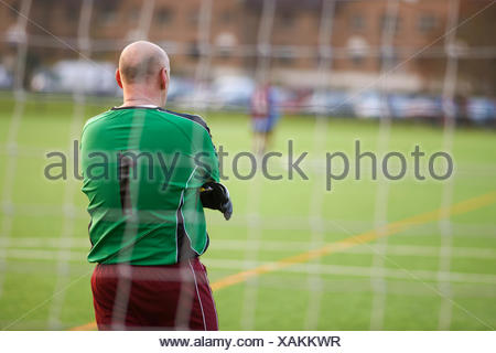 Rearview of goalie at football game - Stock Photo