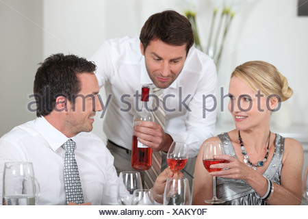 Man serving rose wine at a dinner party - Stock Photo
