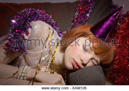 woman with party hat asleep on sofa - Stock Photo