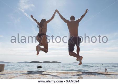 Young couple jumping into sea, rear view, Orebic, Croatia - Stock Photo