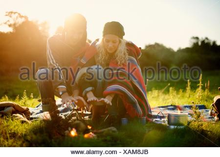 Young camping couple warming hands by campfire at dusk - Stock Photo