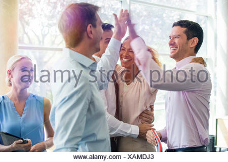 Colleagues giving each other high-five - Stock Photo