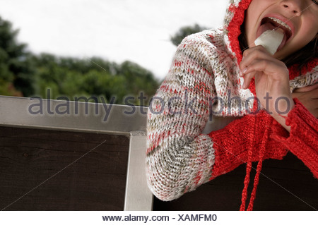 A young girl leaning over a fence, eating an ice cream bar - Stock Photo