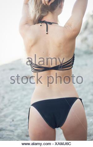 Blond woman in a black bikini on a sandy beach. - Stock Photo