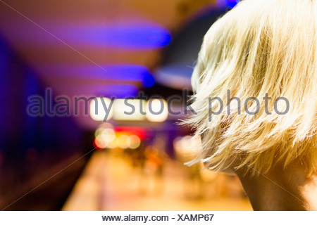 Germany, Bavaria, Munich, Young woman waiting in metro station - Stock Photo