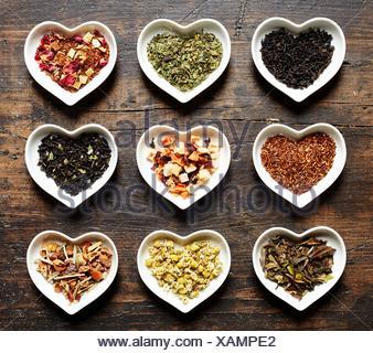 Herzchen Schalen mit neun unterschiedlichen Teesorten auf Holz Hintergrund in rustikalem Stil - Stock Photo