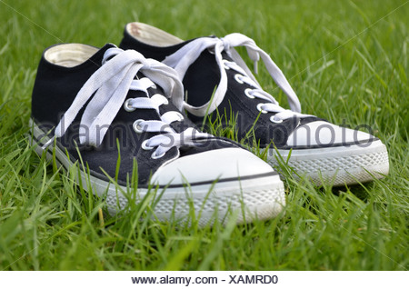 Chuck Taylor All Stars or Chucks sneakers in the grass - Stock Photo