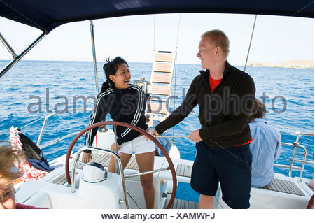 Happy teenage boy and girl steering a sail boat in the sea - Stock Photo