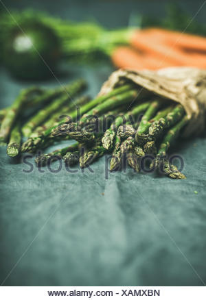 Fresh seasonal vegetables on table. Green asparagus, carrots and avocado at background over grey linen table cloth. Copy space, selective focus. Clean - Stock Photo