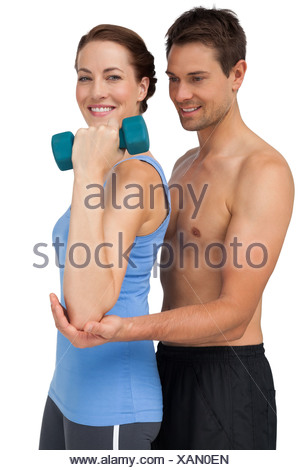 Male trainer assisting woman with dumbbell - Stock Photo