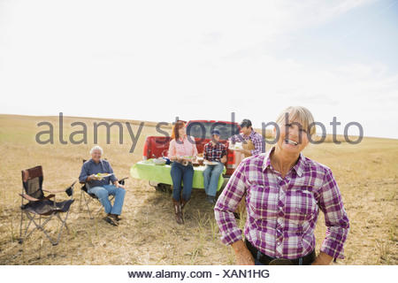 Multi-generation family enjoying lunch in crop field - Stock Photo