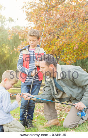 Father teaching sons to prepare fishing rods - Stock Photo