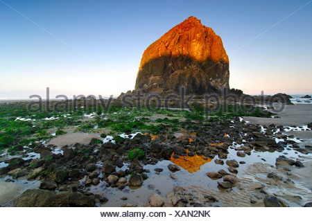 Famous 'Haystack Rock' monolith, solidified lava rock at Cannon Beach, tourist attraction, Clatsop County, Oregon, USA - Stock Photo