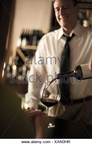 Bartender pouring red wine in bar Stock Photo
