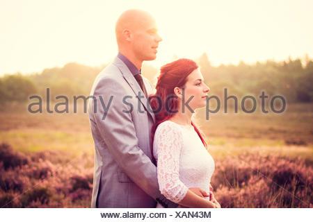 newlywed couple embracing outdoors - Stock Photo
