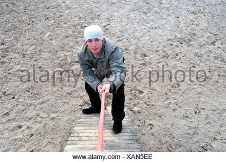 Teenager, 18 years old, climbing up a rope - Stock Photo
