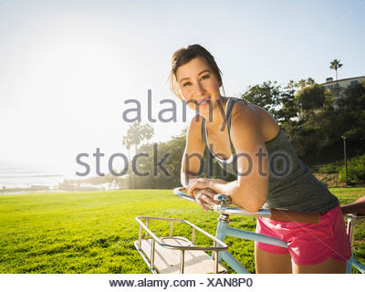 Young woman with bicycle in park - Stock Photo