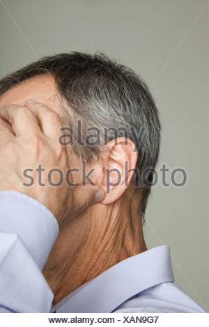 Mature man holding head, cropped - Stock Photo