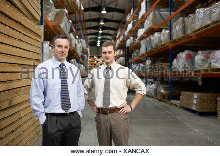 Two businessmen in warehouse, portrait - Stock Photo