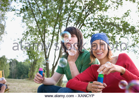 Germany, Young couple blowing bubbles - Stock Photo