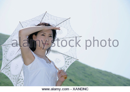 A young woman standing with parasol - Stock Photo