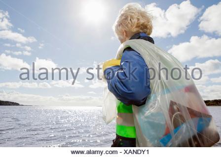 Boy hauling bag of trash on beach - Stock Photo