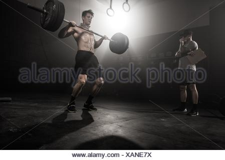 Mid adult man lifting barbell, while trainer looks on, low angle view - Stock Photo
