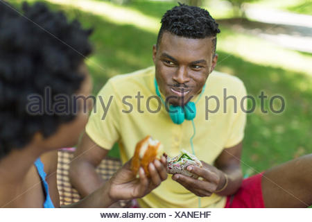 Young couple in park picnicing on sandwiches - Stock Photo