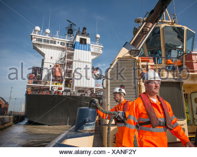 Workers on tug boat pulling in rope - Stock Photo