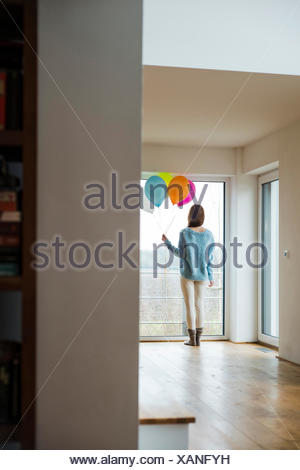 Young woman holding bunch of balloons looking out of window - Stock Photo