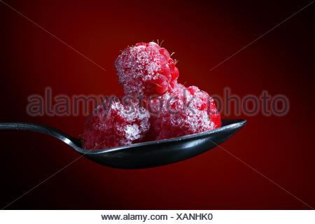 Color photo of pile of red rasberry on metal spoon - Stock Photo