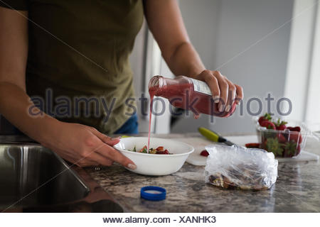 Mid section of woman pouring syrup in chopped strawberry at home - Stock Photo