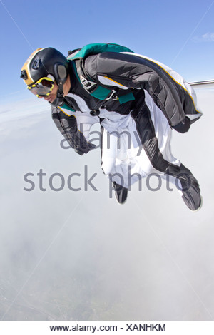 Mid adult man free falling in wingsuit preparing to fly - Stock Photo