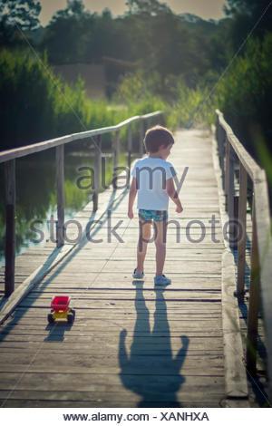 Boy pulling a toy truck across a bridge - Stock Photo