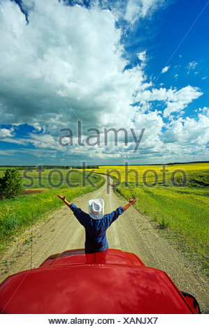 Man sits on the front of apick-up a truck on a country road with farmland in the background, Tiger Hills, Manitoba, Canada - Stock Photo