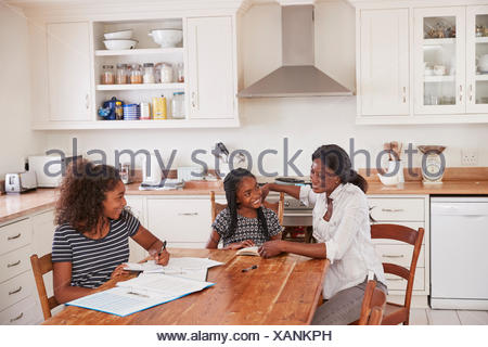 Mother Helping Two Daughters Sitting At Table Doing Homework - Stock Photo