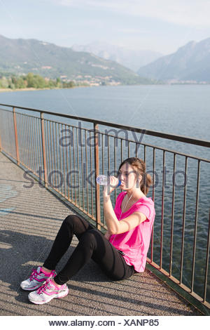 Italy, Lecco, sportive young woman drinking water after running at lakeshore - Stock Photo