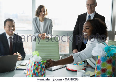 Businesswoman opening birthday gifts from colleagues in conference room - Stock Photo
