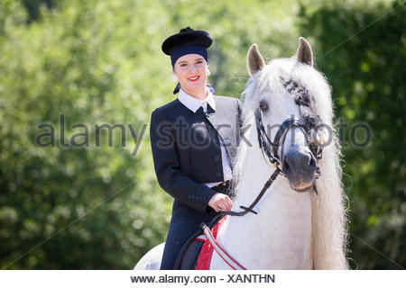 Pure Spanish Horse, Andalusian. Rider in traditional dress on gray stallion on a riding place. Austria - Stock Photo