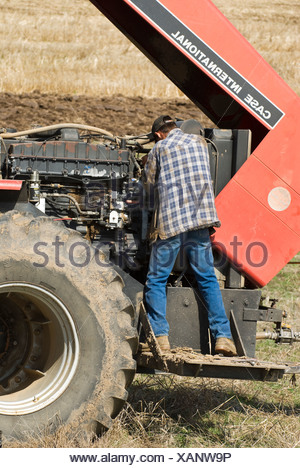 A farmer performs maintenance on a tractor in the field during planting season / near Pullman, Palouse Region, Washington, USA. - Stock Photo