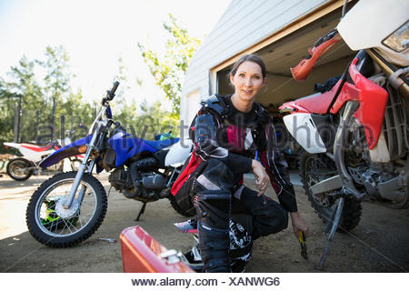 Portrait smiling woman fixing motorbike in driveway - Stock Photo