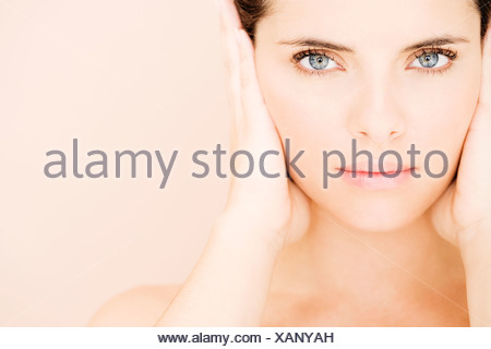 Portrait of young woman's face with hands over her ears, hear no evil - Stock Photo