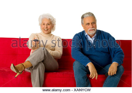 elderly couple on the sofa with television remote control - Stock Photo