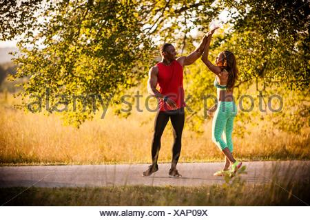 Young running couple giving high fives in park - Stock Photo