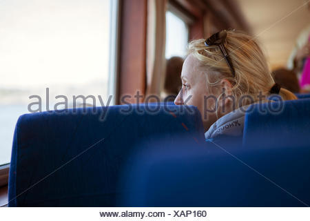 Sweden, Gothenburg Archipelago, Vastergotland, Styrso, Mature blonde woman looking through train window - Stock Photo