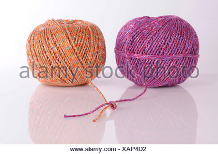 Two balls of cord used for recycling tied together - Stock Photo