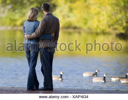 Rear view of a woman and man by a lake - Stock Photo