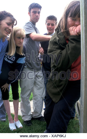 group of teenagers bullying young girl in park - Stock Photo